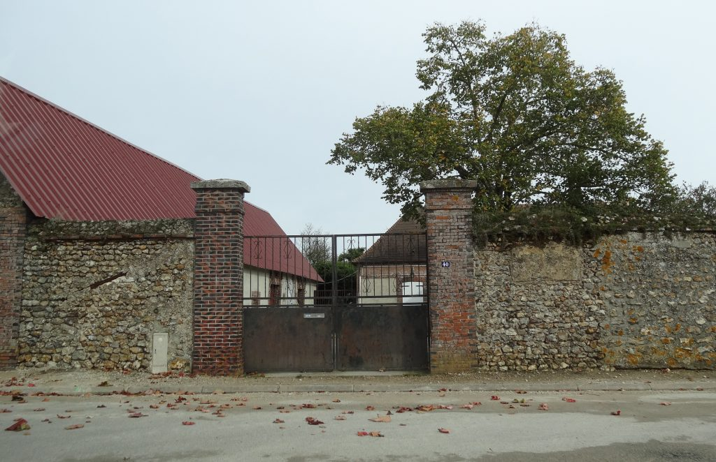 Imposing iron gate surrounded by stone wall, family farm in background