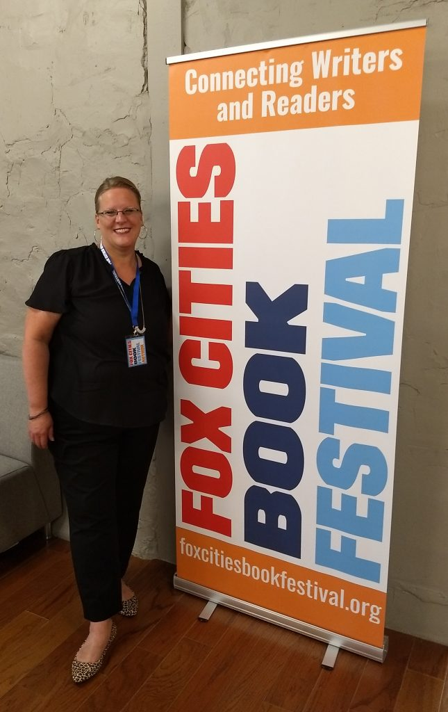 "Carolyn Porter standing next to a large banner that reads ""Fox Cities Book Festival."""