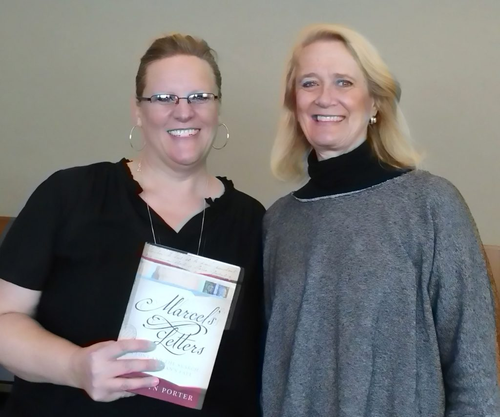 "Photo of Sunny Nelson and Carolyn Porter, who is holding a copy of the book ""Marcel's Letters"""