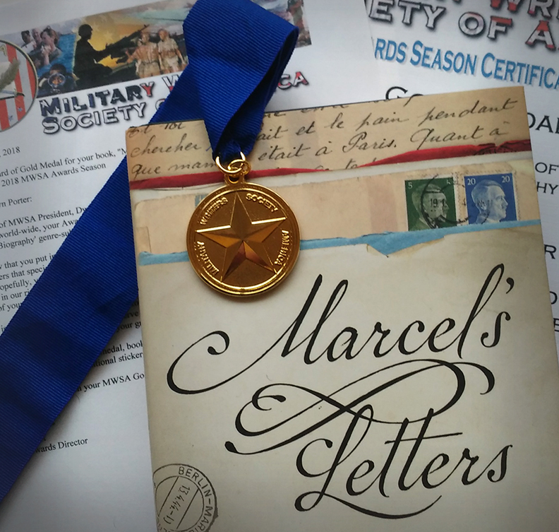 "Gold Medal from Military Writers Society of America laying on top of book ""Marcel's Letters"""