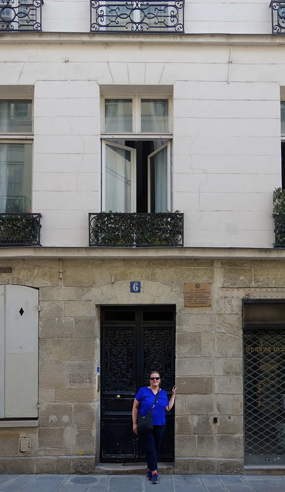 Carolyn Porter standing in front of 6 Rue de Regrattier, Ile Saint Louis, Paris, WWII home of Louise Dillery
