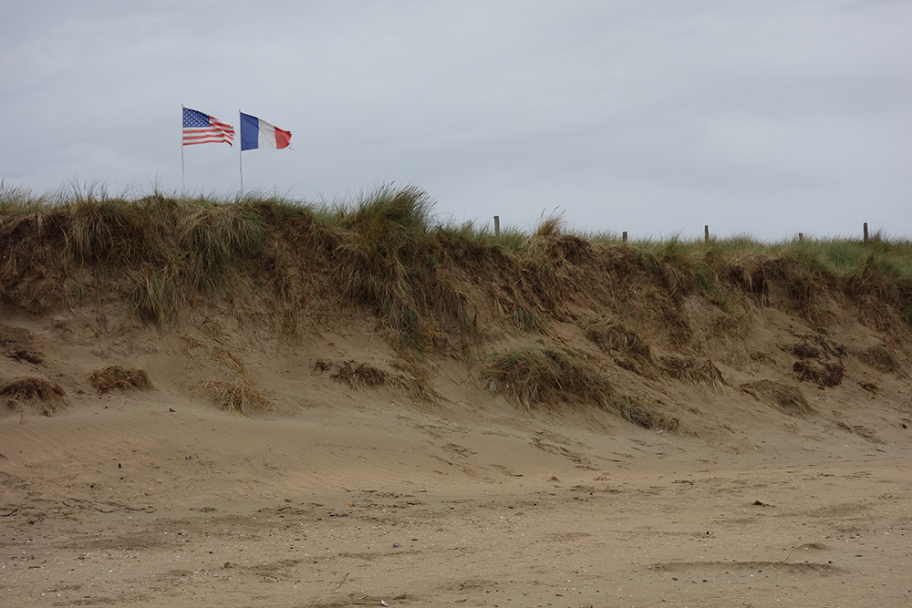 Utah beach, Normandy, with American and French flags flying in distance